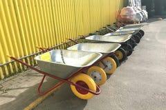Uma fileira dos carrinhos de mão do jardim expostos na rua perto de uma loja da construção fotos de stock royalty free