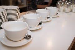 Uma fileira dos copos brancos Fotografia de Stock Royalty Free