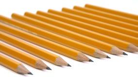 Uma fileira dos lápis em uma superfície branca filme