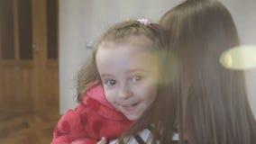 Uma filha pequena apressa-se nos braços do ` s da mãe em casa e dá-se lhe um abraço grande video estoque
