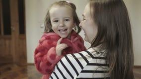 Uma filha pequena que abraça sua mãe filme