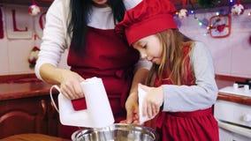 Uma filha que adiciona na bacia um açúcar e uns ingredientes de mistura da mãe com misturador vídeos de arquivo