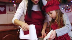 Uma filha que adiciona na bacia um açúcar e uns ingredientes de mistura da mãe com misturador video estoque