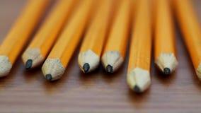 Uma filtração disparou de uma fileira dos lápis que descansam em uma tabela de madeira vídeos de arquivo