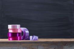 Uma fita colorida do cetim no rolos em uma tabela de madeira, com espaço escuro abstrato do fundo e da cópia Fotos de Stock