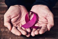 Uma fita cor-de-rosa nas mãos de um homem imagens de stock