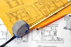 Uma fita de medição e um lápis em um azul da planta de assoalho imagem de stock