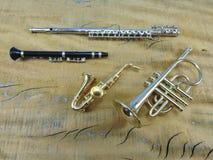Uma flauta transversal, um clarinete, um saxofone e uma trombeta em uma superfície de madeira fotografia de stock royalty free