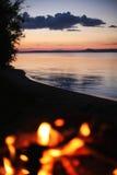 Uma fogueira perto de um lago Fotos de Stock