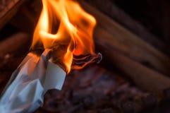 Uma folha de papel que queima-se com uma chama brilhante alaranjada vermelha com calor imagens de stock