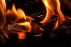 Uma folha de papel que queima-se com uma chama brilhante alaranjada vermelha com calor imagem de stock royalty free