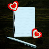Uma folha de papel vazia, a pena e os dois corações em um fundo de madeira Imagens de Stock Royalty Free