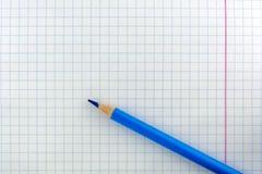 Uma folha do livro de exercício em uma gaiola O lápis é azul na folha foto de stock royalty free