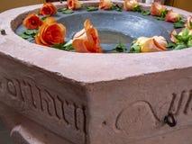 Uma fonte batismal decorada com rosas, detalhe imagens de stock