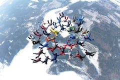 Uma formação de skydivers está no céu do inverno fotografia de stock