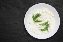 Uma foto aérea do requeijão natural fresco em uma bacia cerâmica branca na mesa de pedra preta Aneto verde Eco orgânico saudável imagens de stock royalty free