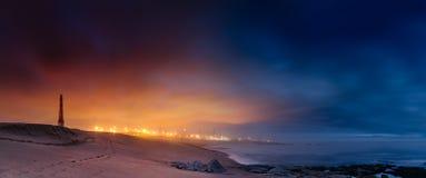 Uma foto na noite na praia com cidade ilumina-se no fundo fotografia de stock royalty free