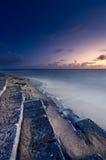 Cena surreal do litoral do crepúsculo com as escadas que atravessam o mar imagens de stock royalty free