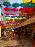 Uma foto colorida dos guarda-chuvas em uma arcada da compra Foto de Stock
