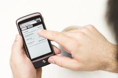 O homem verifica detalhes de operação bancária móveis em Smartphone Imagem de Stock