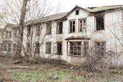 Uma foto de uma casa da quinta abandonada velha e terrível, que se deteriore eventualmente, coberto de vegetação com as árvores v imagem de stock royalty free