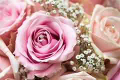 Uma foto macro colorida de um ramalhete detalhado com rosas cor-de-rosa, as flores pequenas brancas e um diamante falsificado no  fotografia de stock