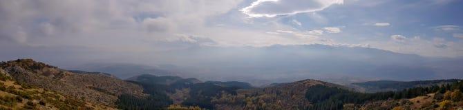 Uma fotografia da silhueta das montanhas com névoa e luz do sol imagens de stock royalty free