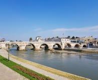 Uma fotografia do rio que passa sob a ponte de pedra foto de stock