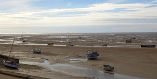 Uma frota dos barcos saiu encalhada na maré baixa Imagens de Stock
