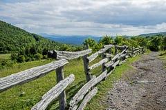Uma fuga de caminhada segue uma cerca de trilho rachado abaixo da montanha em Grayson Highlands imagens de stock