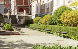 Uma fuga pisada pavimentada da aleia em um parque bonito quadro com arbustos e os bancos cortados para o resto Imagem de Stock