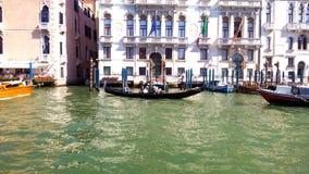 Uma gôndola transporta seus passageiros através de um canal em Veneza fotografia de stock