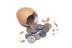 Uma galinha coloca um ovo e há dinheiro para dentro Fotos de Stock