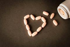 Uma garrafa aberta dos comprimidos no fundo escuro Comprimidos Heart-Shaped imagens de stock