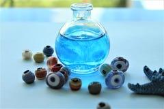 Uma garrafa cumpre com água azul fotos de stock