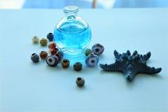 Uma garrafa cumpre com ?gua azul imagens de stock