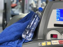 Uma garrafa da água e uma toalha estão no instrumento do treinamento foto de stock