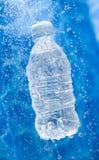 Uma garrafa de água em um respingo da água fotos de stock