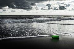 Uma garrafa de vidro é jogada para fora para o litoral fotografia de stock royalty free