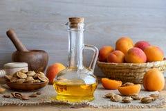 Uma garrafa do óleo de núcleo do abricó com abricós frescos fotografia de stock royalty free
