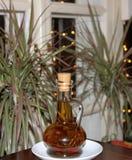 Uma garrafa do azeite na tabela com as plantas no fundo Fotos de Stock Royalty Free