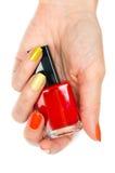 Uma garrafa do verniz para as unhas vermelho em uma mão fêmea Imagens de Stock