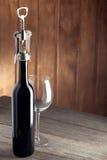 Uma garrafa do vinho é um corkscrew e um vidro na tabela de madeira velha Fotografia de Stock