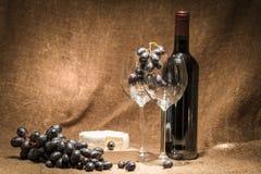 Uma garrafa do vinho com dois vidros vazios Foto de Stock