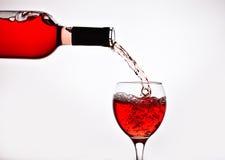 Uma garrafa do vinho cor-de-rosa derrama no vidro Fotografia de Stock