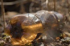 Uma garrafa marrom jogada nas madeiras lixo fotografia de stock
