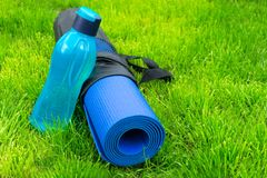 Uma garrafa ou uma água em uma esteira da ioga na grama verde fresca O conceito do treinamento e da recreação esportes e sa?de Sa fotos de stock royalty free