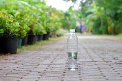 Uma garrafa plástica da água potável que desarruma no caminho do parque com o fundo verde da natureza para um conceito de limpeza imagem de stock