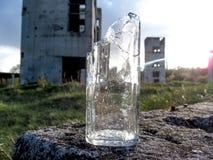 Uma garrafa quebrada está em um lote vago na frente de duas torres destruídas Imagem de Stock Royalty Free