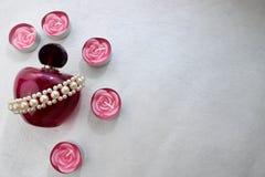 Uma garrafa transparente de vidro bonita cor-de-rosa do perfume fêmea decorou com as pérolas monótonos brancas e velas cor-de-ros Fotos de Stock